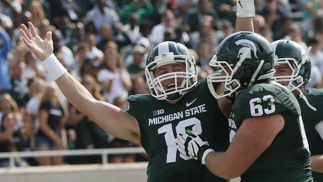 Michigan State's Connor Cook (18) celebrates his first quarter touchdown with offensive lineman Travis Jackson (63), right, against Eastern Michigan in their football game in East Lansing on Saturday, September 20, 2014. The Spartans beat the Eagles, 73-14.