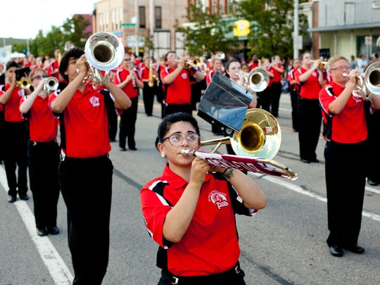 A trombone player marches in the Big Reds marching band during the Rotary International Day Parade in downtown Port Huron.