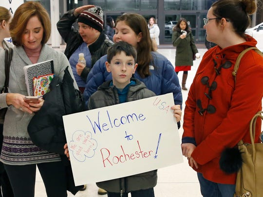 John Collins, 10, of Pittsford, holds a welcome sign