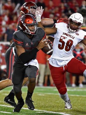Houston quarterback Greg Ward Jr., left, scrambles past Louisville linebacker Jonathan Greenard (58) during the second half of their game Thursday in Houston.