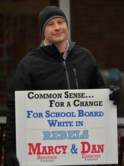 Dan Emmons, a write-in candidatge for the South Burlington School Board, holds a sign for himself and fellow write-in candidae Marcy Brigham on Town Meeting Day, March 7, 2017, outside of Orchard School, one of South Burlington's polling stations.