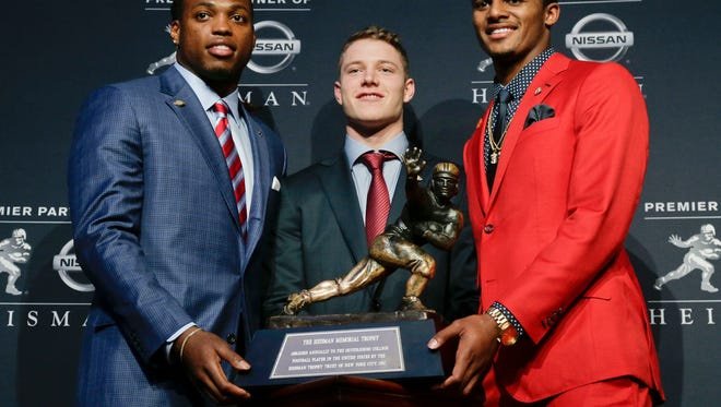 Heisman Trophy finalists, from left, Alabama's Derrick Henry, Stanford's Christian McCaffrey and Clemson's Deshaun Watson pose for a photo with the Heisman Trophy before the start of the award presentation show, Saturday, Dec. 12, 2015, in New York. (AP Photo/Julie Jacobson)