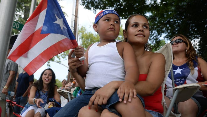 Jeniel Beltran, 6, and his mother Jessica Orengo, of Vineland, wave a Puerto Rican flag while watching the Puerto Rican Festival of New Jersey parade, Sunday Jul. 26, 2015 in Vineland.