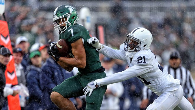 Michigan State Spartans wide receiver Cody White (7) attempts to make a  catch against Penn State Nittany Lions cornerback Amani Oruwariye (21) during the first half of a game at Spartan Stadium.