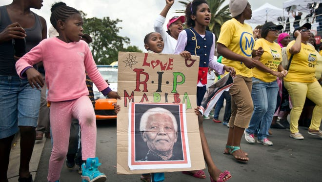 "A young girl with a placard showing the face of Nelson Mandela and referring to his clan name ""Madiba,"" marches with others to celebrate his life, in the street outside his old house in Soweto, Johannesburg, South Africa, Dec. 6, 2013."