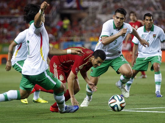 Spain's Pedro Rodriguez, second left, vies for the ball as Bolivia's Damir Miranda, right, and Luis Gutierrez, second right, looks on during their friendly soccer match in Seville, on Friday, May 30. 2014. (AP Photo/Miguel Angel Morenatti)