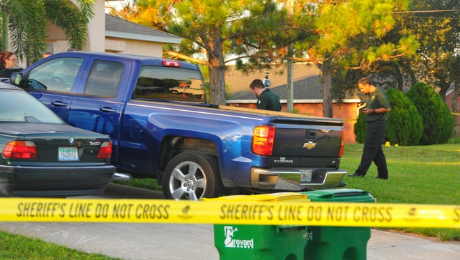 Investigators and crime scene technicians  at the scene of a deputy shooting in Port St. John. Yellow evidence markers dot the yard and street in front of the house.