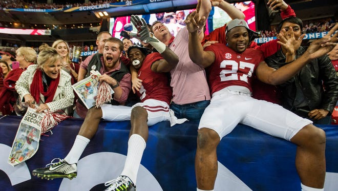 Alabama wide receiver Calvin Ridley (3) and defensive back Shawn Burgess-Becker (27) celebrate with fans following the SEC Championship Game in Atlanta, Ga. on Saturday December 5, 2015.