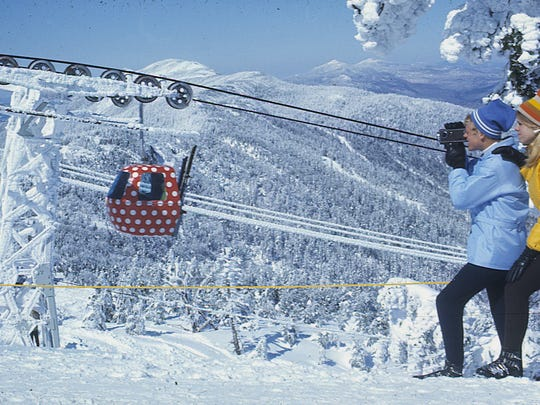 Historic photo shows a couple filming near the summit of Sugarbush's gondola.