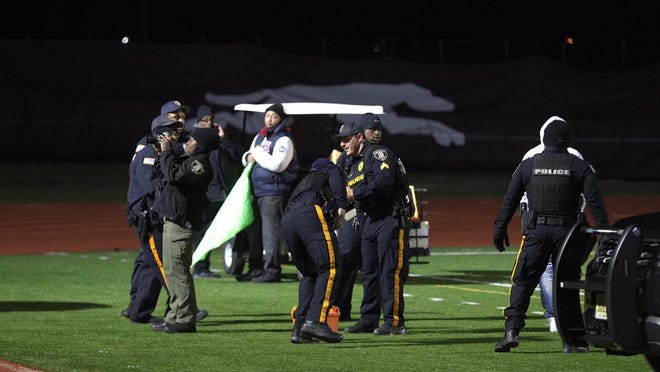 Police investigate the scene after a gunman shot into a crowd of people during a football game at Pleasantville High School in Pleasantville, N.J., Friday, Nov. 15, 2019. Players and spectators ran for cover Friday night when a gunman opened fire at the New Jersey high school football game. (Edward Lea/The Press of Atlantic City via AP)