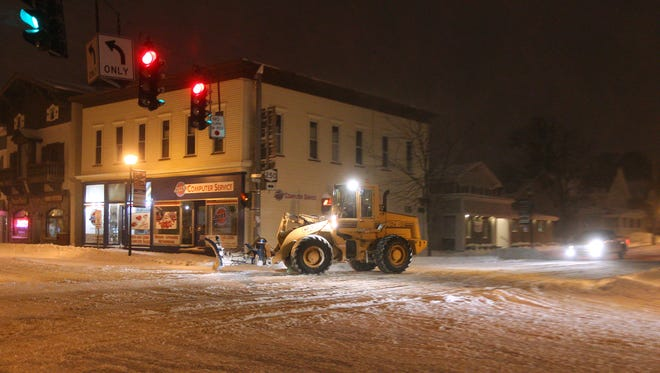 A snowplow clears an intersection on Main Street in Webster, early this morning.