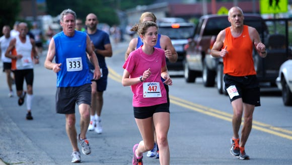Runners make their way through town during a past Rhododendron
