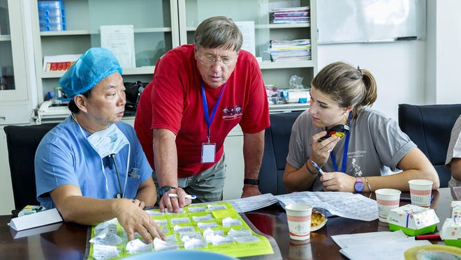 Rich Gangwish helps create a surgery schedule with medical staff during his 2016 trip to China with Operation Smile. At left is Willie Go, former field medical director and anesthesiology leader, who was the chief medical officer for the Asian Region of Operation Smile. Gangwish is at center. At right is Caroline Kimberly, the Operation Smile mission coordinator from Virginia Beach.