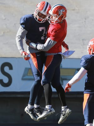 Quarterback Mark Torrez, right ,and receiver Kavika Johnson celebrate their touchdown pass/reception during Wednesday's scrimmage at the Sun Bowl.