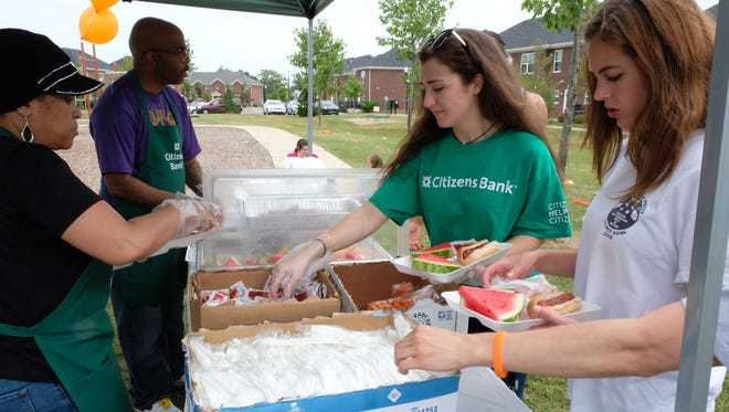 Volunteers from Gleaner's and Citizen Bank prepare lunches for children at kick off event Saturday.