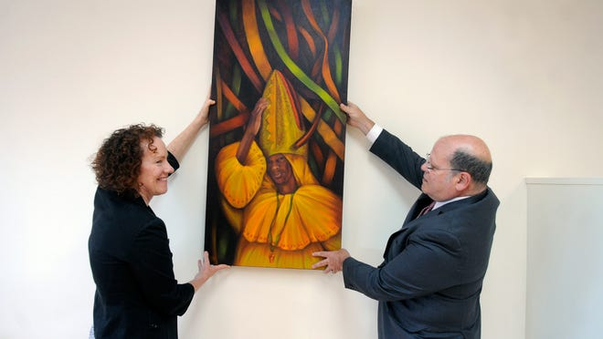 Arts Mid-Hudson Executive Director Linda Marston-Reid and Chairman Paul Tesoro handle a painting Tuesday at the group's new office in the Town of Poughkeepsie. The painting is the work of Pablo Shine, who originally is from Puerto Rico and is a SUNY Ulster faculty member.