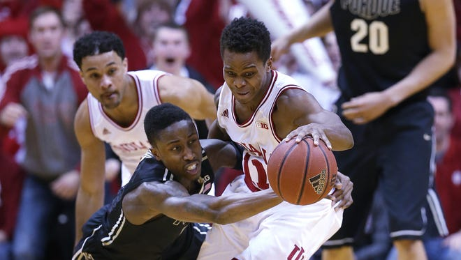 Purdue Boilermakers guard Jon Octeus fouls Indiana Hoosiers guard Yogi Ferrell while going for a loose ball in the second half. Indiana hosted Purdue at Assembly Hall on Feb. 19, 2015.