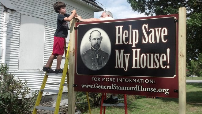 From left: Evan Kaigle and Charlie Farrell add the finishing touches to the sign in front of the General Stannard House in September 2014.
