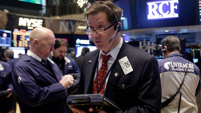 Trader Christopher Forbes, center, works on the floor of the New York Stock Exchange.