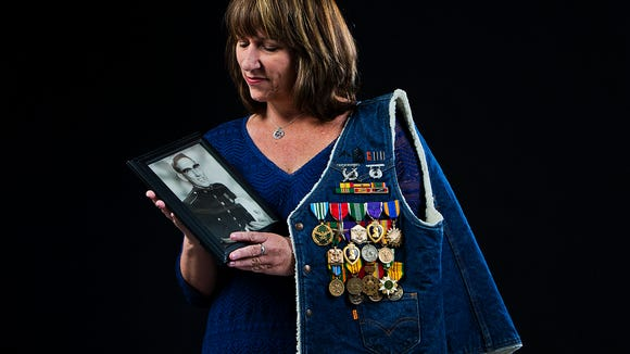 Republic columnist Karina Bland holds a photo of her father,Capt. David John Bland, with his many medals. The decorated Vietnam War veteran retired from the Marine Corps in 1979 after 21 years of service.