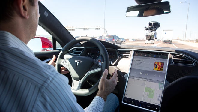 Republic Reporter Ryan Randazzo keeps his hands near the steering wheel as he tests the self-driving car technology in the Tesla Model S P90D in Scottsdale, Ariz. on Feb 26, 2016.
