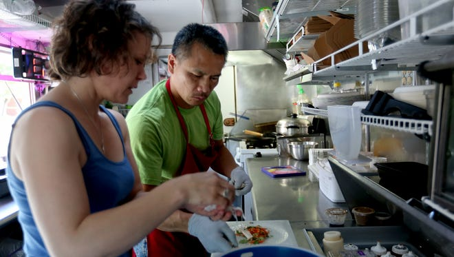 Carmen and Minh Nguyen work in their Fusion Semi-Authentic Vietnamese Food Truck at the Oregon National Guard campus in Salem on May 11, 2016.