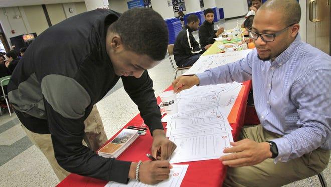 FILE – Chris Hawkins, right, will be Crispus Attucks' new boys basketball coach in 2016-17.