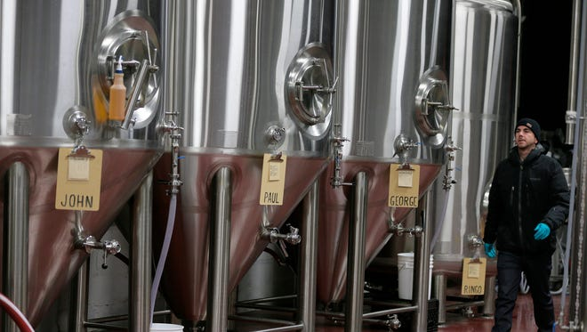 Sean Campbell walks past fermenters at the Asbury Park Brewery on Feb. 15, 2017.