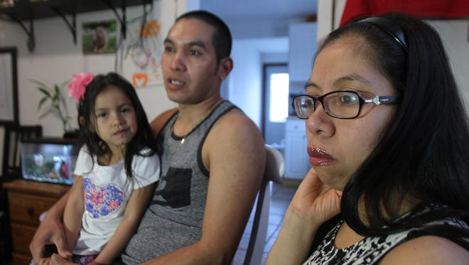 Angelica Avila listens as her husband Carlos Larios speaks during an interview in their Long Branch home Thursday, March 30, 2017, with their daughter Kimberly Larios, 3.  Both are Guatemalan nationals who illegally entered the U.S. and have lived here for more than a decade (Larios in since 2005, Avila since 2006).