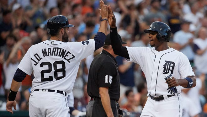 Tigers rightfielder J.D. Martinez (28) and leftfielder Justin Upton (8) congratulate each other after scoring in the fourth inning of the 13-4 win over the Rays Friday at  Comerica Park.