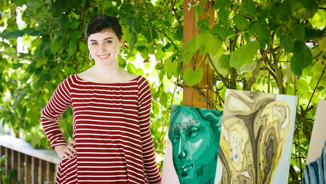 Eilish Gormley poses for a photo with some of her paintings on her patio in Sublimity on Friday, July 7, 2017. The 19-year-old began painting just before high school and has been selected for the Emerging Artist program for the Salem Art Fair.
