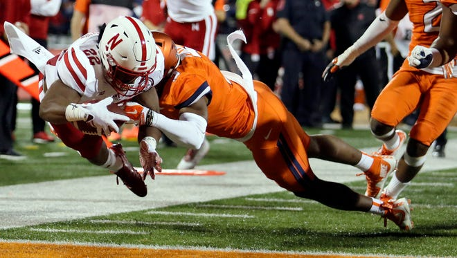 Nebraska running back Devine Ozigbo dives into the end zone for a touchdown against Illinois linebacker Del'Shawn Phillips during the first half Friday.