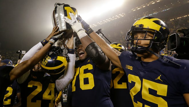Michigan players include defensive back Lavert Hill (24), offensive line Juwann Bushell-Beatty (76) and defensive back Benjamin St-Juste (25) raise the Little Brown Jug to celebrate 33-10 victory over Minnesota at the Michigan Stadium in Ann Arbor, Saturday, November 4, 2017.