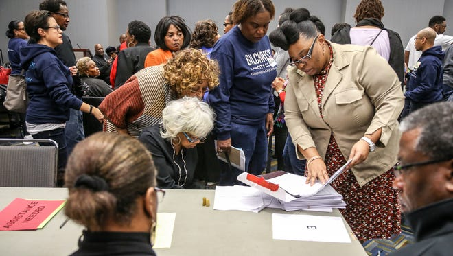 Jennifer Redmond, Detroit elections assistant director, reads the number on an envelope after opening the sealed ballot box during a recount for city clerk at Cobo Center in Detroit on Tuesday, Dec. 5, 2017.