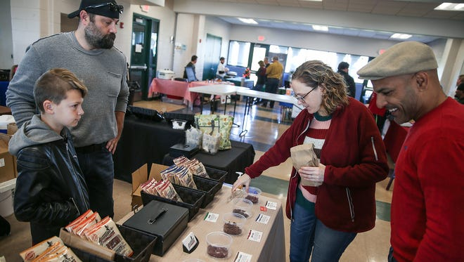 From left, Jacob Piercy and son Alexander, 10, sell Grandpa's Beef Jerky, as customers Nicole Dunton and Jamie Colon browse at the Fishers Winter Farmers Market at Roy G. Holland Memorial Park, Fishers, Ind., Saturday, Dec. 2, 2017. Piercy's craft beef jerky is inspired by memories of making jerky with his grandfather, who was an avid hunter.