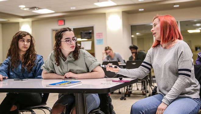 """From left, Carmel students Isabella Fallahi, Josie Cruzan and Indianapolis International School student Romy Candon exchange ideas, Saturday, March 17, 2018, in a planning meeting for Indiana's portion of the national March for our Lives rally to end gun violence. The three are a few of the dozen or so local students working with non-profit """"We LIVE Indy"""" and its president Brandon Warren for the march."""