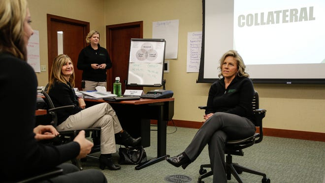 Lindsey Rodriguez (center) takes clues from Chelsa LaFave (left) while playing a pyramid style game during the associate training at the MSU Federal Credit Union in East Lansing.