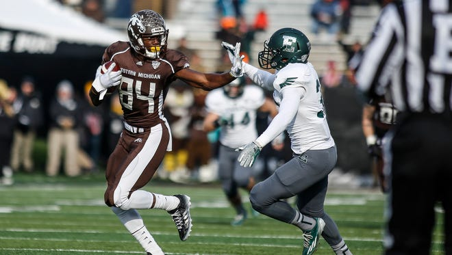 Western Michigan wide receiver Cory Davis (84) tries to run past Eastern Michigan defense back Jason Beck (39) during the first half Saturday  in Kalamazoo.