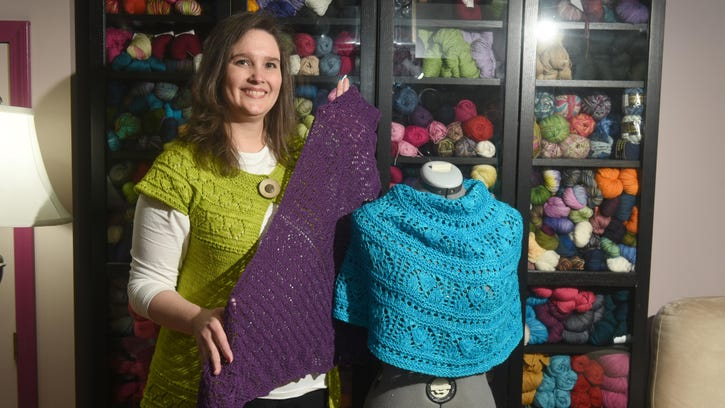 Tina Robbins wears a cap sleeve sweater she knitted using the Tappan Zee pattern, while showing her original designs for a lace-knitted shawl and poncho.