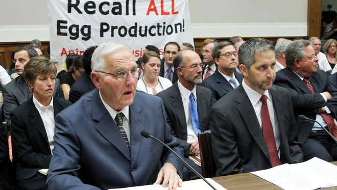 """Protestors unfurl a banner on Capitol Hill in Washington in 2010 as Wright County Egg owner Austin """"Jack"""" DeCoster, left, and Chief Operating Officer Peter DeCoster, right, testify before a House oversight and investigations subcommittee hearing on the outbreak of salmonella contamination in eggs."""
