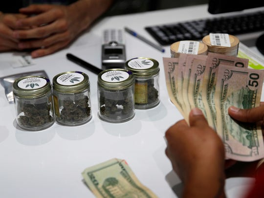In this July 1, 2017 file photo, a person buys marijuana at the Essence cannabis dispensary in Las Vegas.