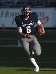Nevada's Ty Gangi escapes the pocket while taking on