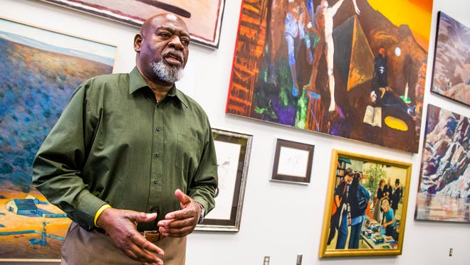 """Gerald Johnson, a volunteer for Friends of Phoenix Public Art, talks about the exhibit """"Gems From the Burton Barr Central Library,"""" currently on display at Phoenix City Hall. The library, which sustained massive damage during a storm, is loaning the art to City Hall."""