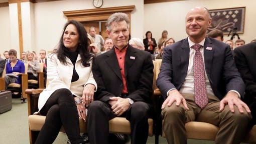 Country singer Randy Travis, center, sits with his wife, Mary, left, and Dr. Blaise Baxter, right, of Erlanger Hospital in Chattanooga, Tenn., before a meeting of the Senate Health and Welfare Committee on Wednesday, Feb. 8, 2017, in Nashville, Tenn. Randy Travis, who suffered a stroke in 2013, attended the hearing for Stroke Awareness Day at the legislature. Dozens of country stars, from Garth Brooks to Kenny Rogers, are scheduled to perform at a tribute show Wednesday night in Nashville to honor Travis.