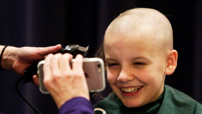 Willem Snyder, 12, of Neenah gets a laugh as his father, Marc, shows him how he looks.