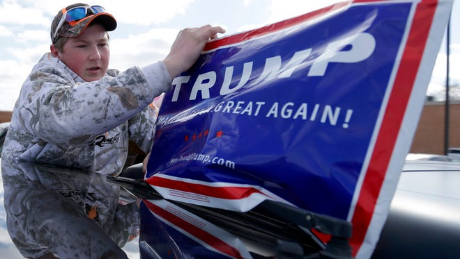 Chris Schwartz of Eau Claire places a sign on his truck Saturday while waiting for Republican presidential candidate Donald Trump  to speak at a rally at Eau Claire Memorial High School.