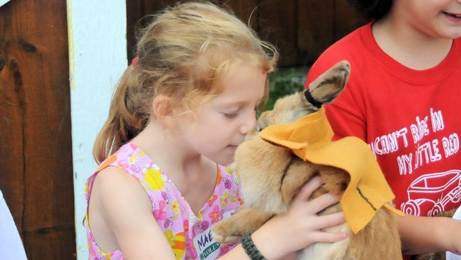 Maeve McGlynn of Kent cuddles with Hop the rabbit on Saturday. Find a photo gallery from the fair at LoHud.com. Maeve McGlynn of Kent and Hop at the Putnam 4H Fair in Carmel on July 28, 2012