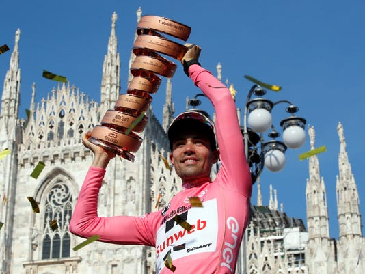 Tom Dumoulin, of the Netherlands, is framed by Milan's gothic cathedral as he holds up the trophy after winning the Giro d'Italia, Tour of Italy cycling race, in Milan, Sunday, May 28, 2017. (AP Photo/Antonio Calanni)