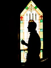 Silhouetted against a stained-glass window at Potterville United Methodist Church, venue pastor Mark Aupperlee preaches on how to go from over-scheduled to organized on Oct. 30, 2016.
