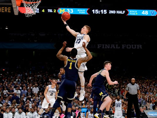Villanova guard Donte DiVincenzo drives to the basket over Michigan guard Charles Matthews (1) during the second half in the championship game of the Final Four NCAA college basketball tournament, Monday, April 2, 2018, in San Antonio. (AP Photo/David J. Phillip)